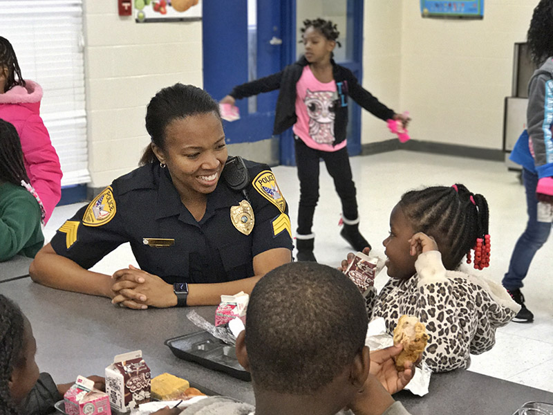 An officer talks to younger kids at a school event